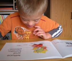 boy with Down syndrom reading