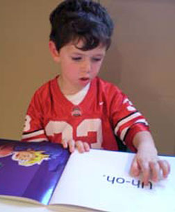 boy with Down syndrom practices reading