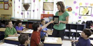 teacher using ipad / tablet to teach kids in class